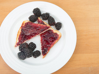 Plate of toast with jam and fresh blackberries