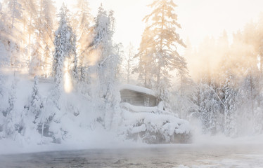 Hut near water and misty forest in winter