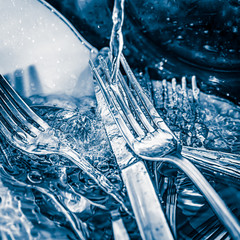 Blue toned image of forks and knives  washed on a sink
