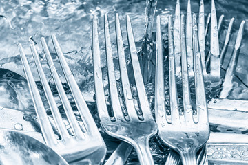 Blue toned silverware being washed with water