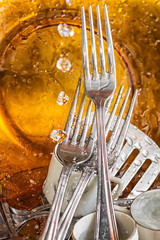 Metallic silverware and dishes washed with water