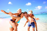 Fototapety Family of four having fun at the beach