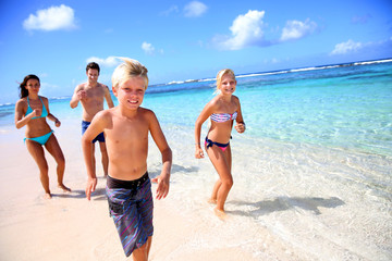 Family running on a paradisaical beach