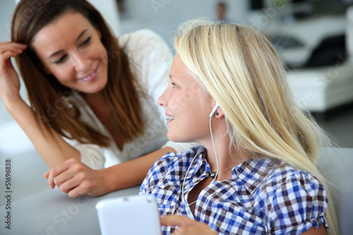 Teenager using smartphone with adult beside her