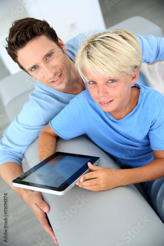 Father and son using digital tablet at home