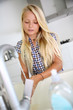 Young girl in kitchen washing her hands
