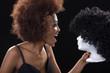 Hübsche Afrikanerin schreit Puppenkopf mit Perücke an