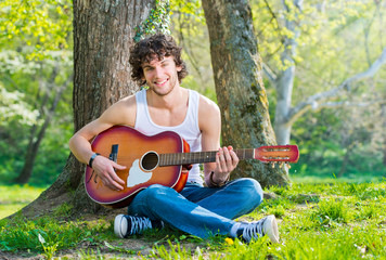 Young man in a park playing guitar