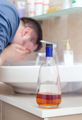 Man with hangover washing up