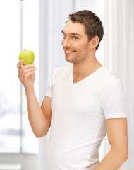 man in white shirt with green apple