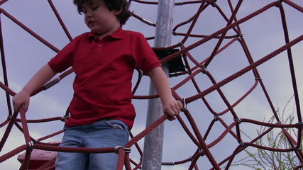 Little boy climbing at park