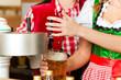 Junge Frau in Tracht zapft ein Bier im Restaurant