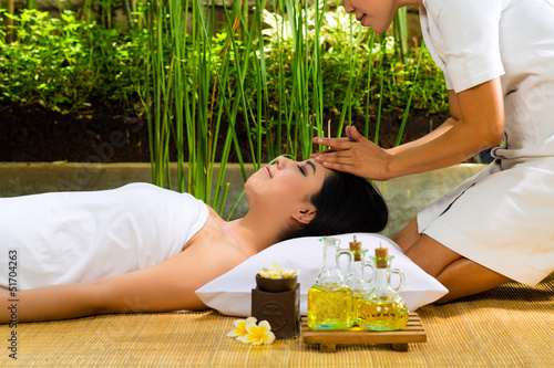 Asian woman having a massage in tropical setting