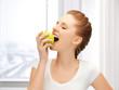 teenage girl biting a green apple