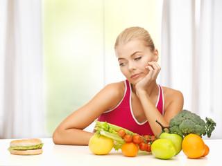 doubting woman with fruits and hamburger
