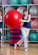 Athletic woman in sports wear exercises with red gym ball