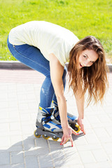 Beautiful teenage girl rollerskating in park