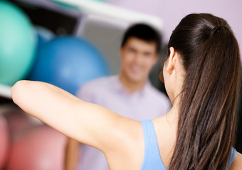 Coach shows exercises to group of people at the gym