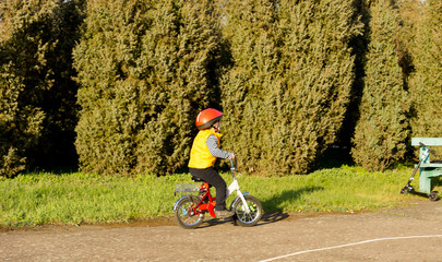 Active little boy riding his bike in the park