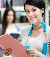 Woman student at the library against bookshelves