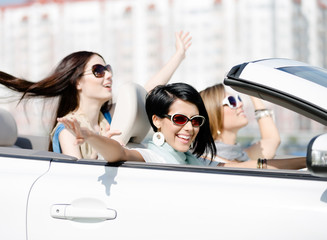 Group of happy girls with outstretched arms in the car