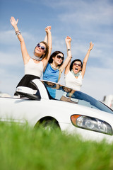 Group of girls stands in the white car with hands up