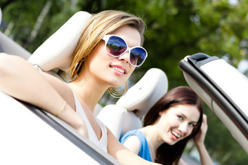 Two girls ride the cabriolet