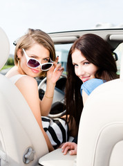 Two girls drive the cabriolet