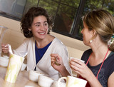 two women taste and compare brewed coffees at a cafe
