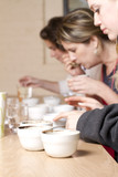 three women taste and compare brewed coffees