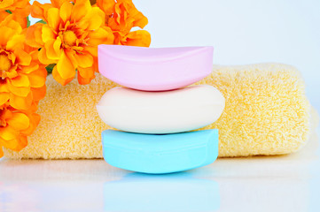 Colored soap bars, yellow towel, flowers