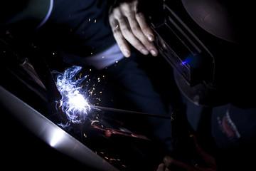 Hombre soldando hierro, acero, metal industrial.