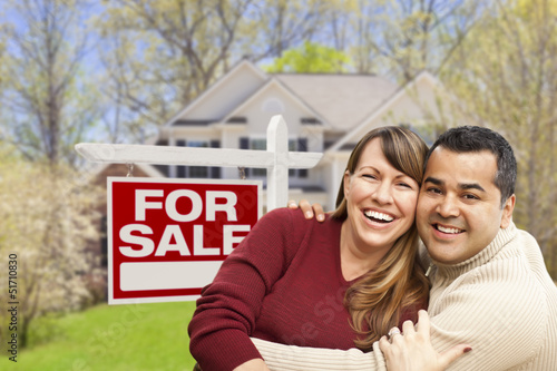 Couple in Front of For Sale Sign and House