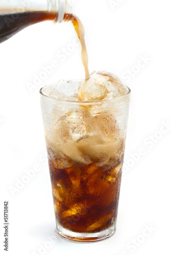 A Bottle of cola soda pouring into a glass filled with ice cubes