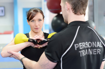 Personal trainer helping young woman with kettle bells