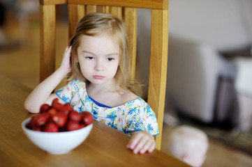 Thoughtful girl with fresh strawberries in a bowl