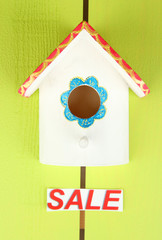 Decorative nesting box and sign on color background
