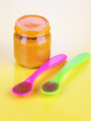 Baby food with weaning spoons on yellow background