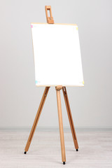 Wooden easel with clean paper in room