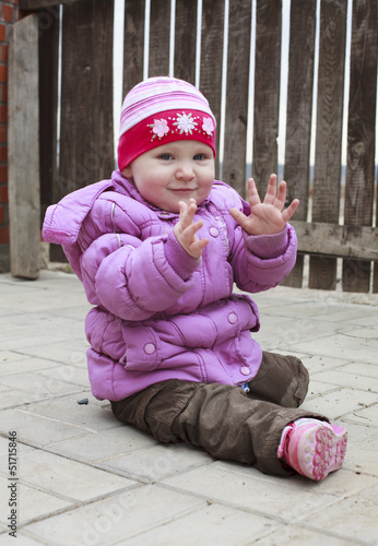 Little cute girl on a walk in the spring in a jacket and knitted