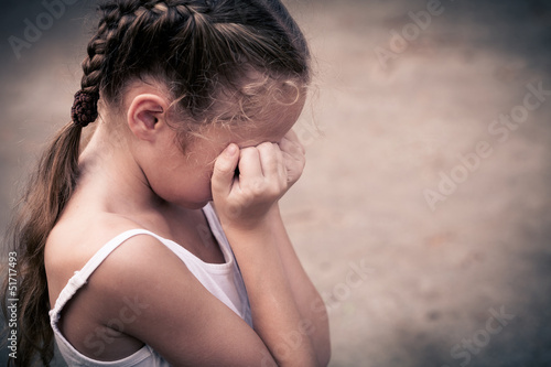 one sad woman sitting on the floor near a wall and holding her h