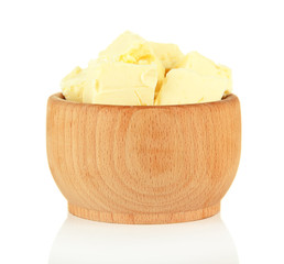 Butter pieces in wooden bowl, isolated on white