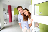 Fototapety Cheerful couple inviting people to enter in home