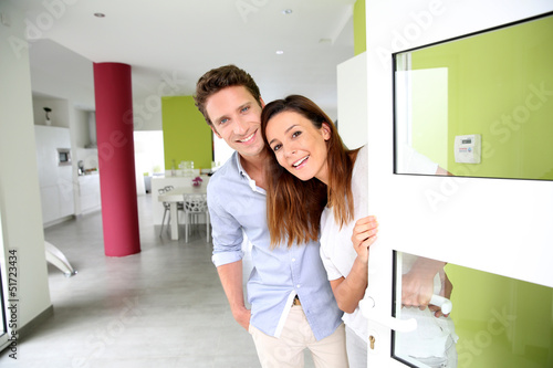Leinwanddruck Bild Cheerful couple inviting people to enter in home