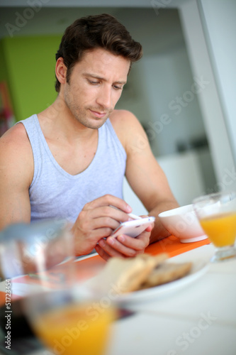 Man using smartphone while having breakfast