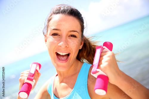 Cheerful girl lifting weights