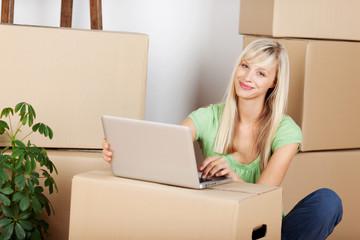 frau sitzt mit ihrem laptop zwischen umzugskartons