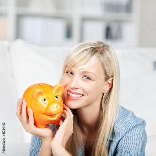 lachende blonde frau hält sparschwein in händen