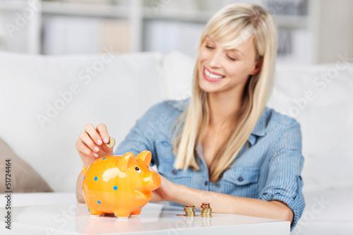 frau wirft geld ins sparschwein