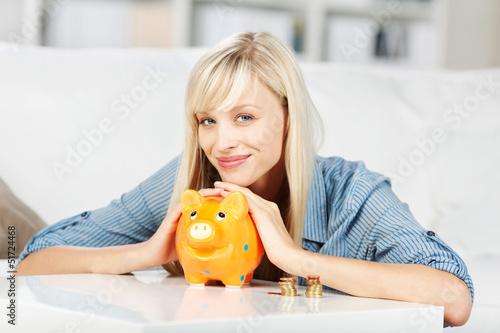 frau hält hände über ihr sparschwein